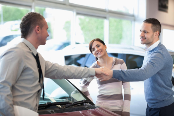 Couple shaking hands with car dealer: MaxAutoPro Auto Advice Blog