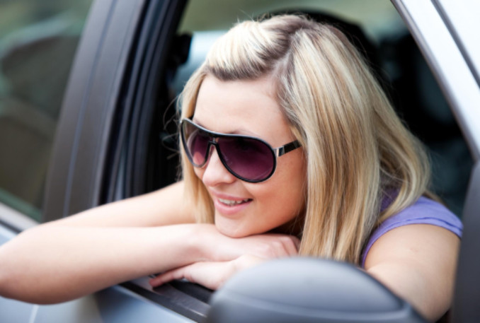 Young woman wearing sunglasses in car: SBDPro Automotive Blog