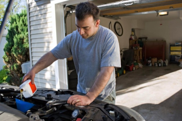 man taking care of car and changing oil