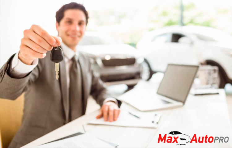 used car salesman handing car keys to buyer